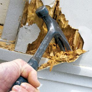 A hammer Picking at Dry Rot- how to sell any house - Mark King Properties